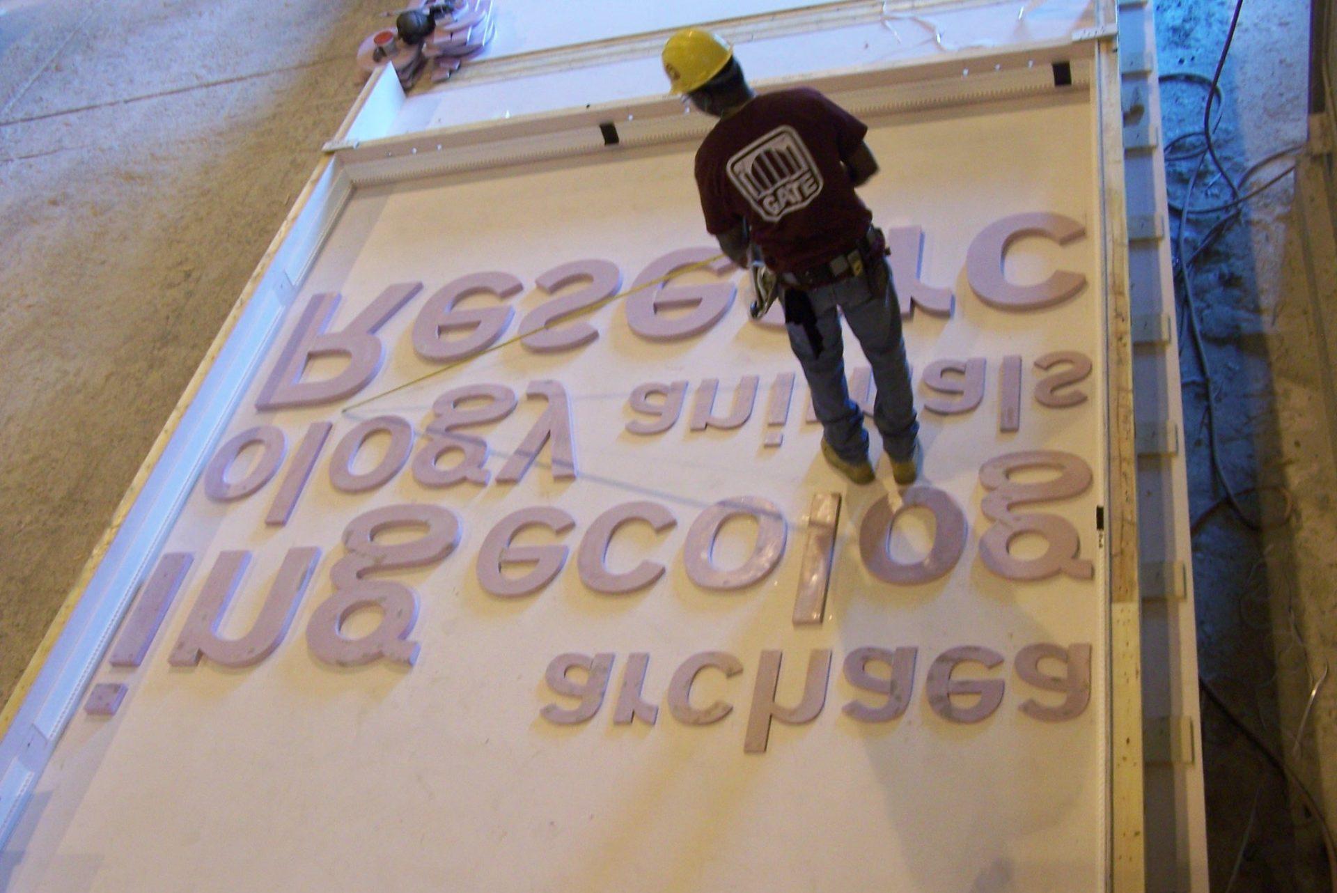 Gate worker setting up precast concrete letters